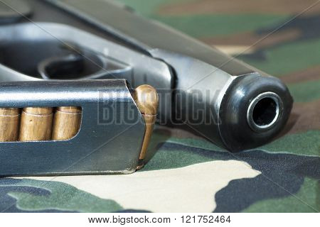 Firearm Pistol  And Hand Gun Ammunition on military camouflage background