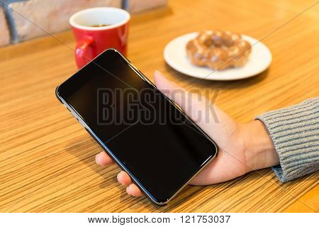 Woman with blank scree of cellphone in cafe