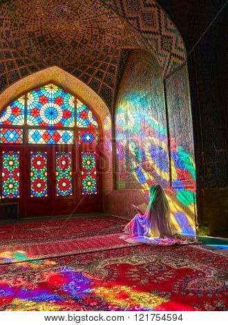 SHIRAZ, IRAN - March 01, 2016: Young Muslim woman praying in Nasir Al-Mulk Mosque (Pink Mosque),   Iran, Shiraz