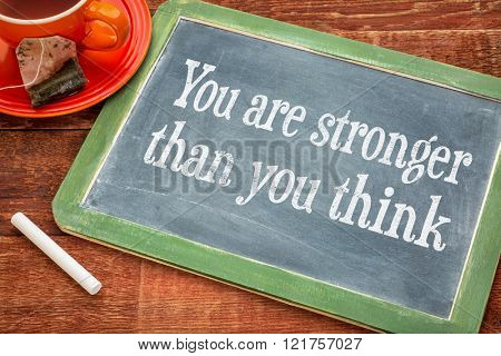 You are stronger than you think - inspirational message - motivational text on a slate blackboard with chalk and cup of tea