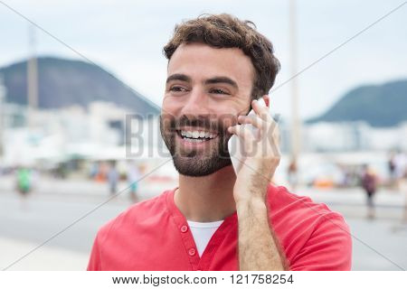 Laughing Man With Red Shirt At Cellphone In The City