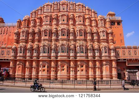 JAIPUR, INDIA - FEBRUARY 27: Unidentified people walk near Hawa Mahal on February 27, 2011 in Jaipur, India. Hawa Mahal was designed by Lal Chand Ustad in the form of the crown of Krishna.
