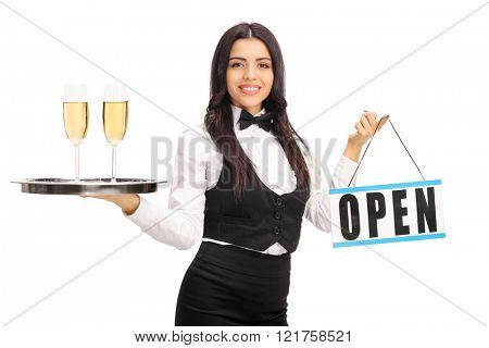 Cheerful waitress holding a tray with two glasses of champagne and an open sign isolated on white background