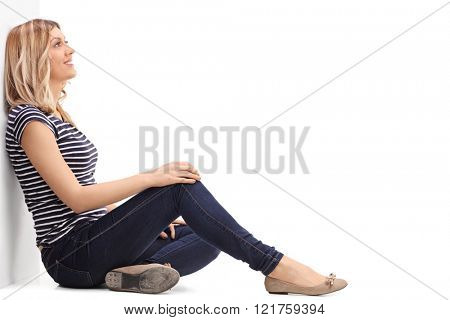 Pensive blond woman sitting on the floor and leaning against a wall isolate on white background
