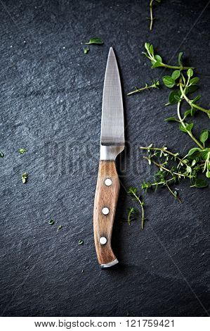 Kitchen knife and herbs on a black slate
