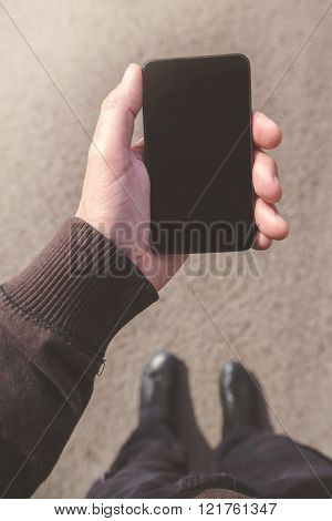 Man Looking At Smartphone Screen While Walking On Street