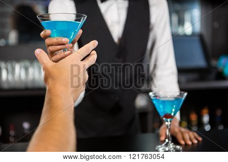 Bartender serving blue cocktail at bar counter in bar