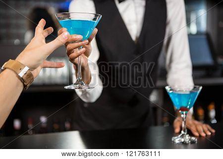 Bartender serving blue cocktail at bar counter in bar