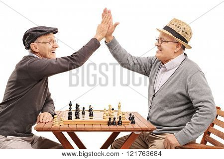 Two senior pals playing chess and high-five each other isolated on white background