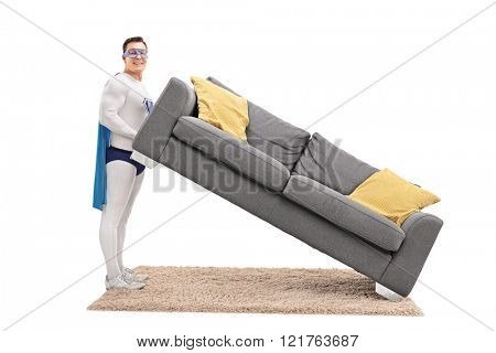 Young man in superhero costume lifting a sofa and looking at the camera isolated on white background