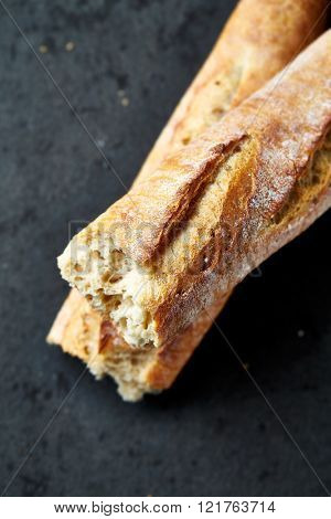 Fresh baguette on a stone background (close up)