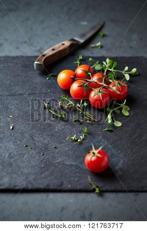 Cherry tomatoes and herbs on a black slate