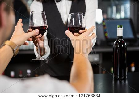 Bartender serving glasses of wine at bar counter in bar