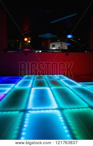 Blue and green illuminated disco dance floor in bar