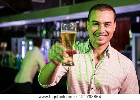 Man posing with glass of beer and friend at bar counter in background