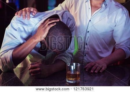 Man comforting his depressed friend in bar
