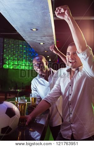 Happy men watching a football match in bar