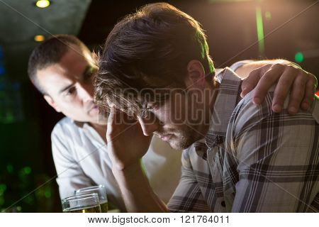 Man comforting his depressed friend in bar
