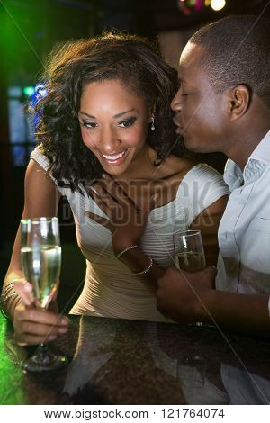 Man kissing a woman while having champagne at bar counter in bar