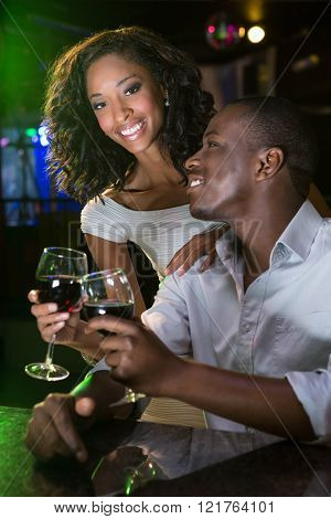 Couple smiling and toasting their wine glasses at bar counter in bar