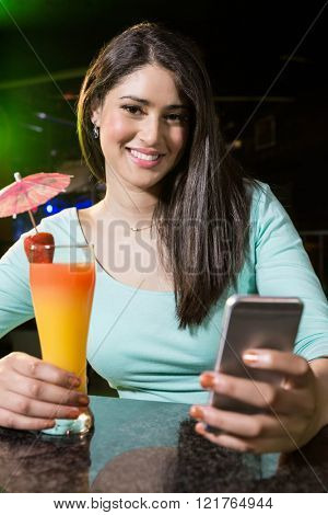 Beautiful woman typing a text message while having cocktail at bar counter
