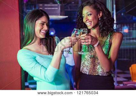 Happy women toasting champagne glasses in bar