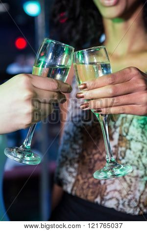 Women toasting their champagne glasses in bar