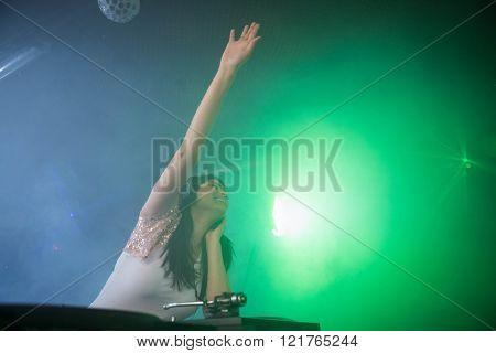 Pretty female DJ waving her hand while playing music at nightclub