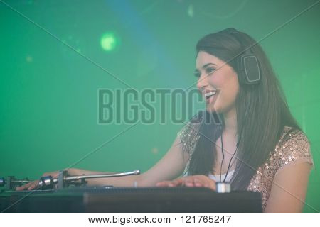 Pretty female DJ playing music at the nightclub