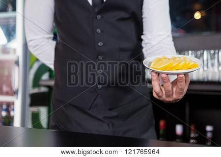 Waiter serving slices of lime at bar counter