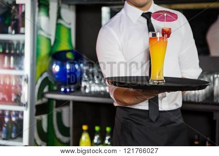 Mid section of bartender serving cocktail in bar