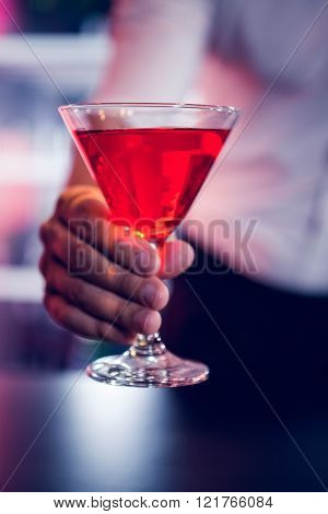 Bartender serving a red martini in bar