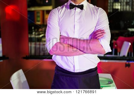 Mid section of waiter standing with his arms crossed in bar
