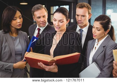 Lawyer reading a law book and interacting with businesspeople in office