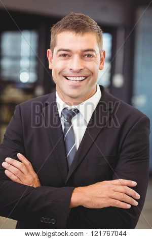 Portrait of businessman standing with arms crossed in office