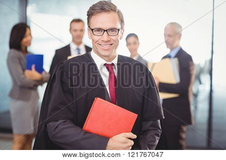 Portrait of lawyer holding a law book in office