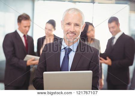 Portrait of businessman using laptop in office