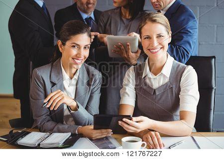 Portrait of businesswomen using digital tablet in conference room