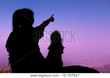 Silhouette Back View Of Mother And Child Hikers Enjoying The View At The Top Of A Mountain.