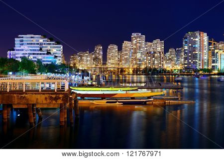 Vancouver city night view with buildings and boat in bay.