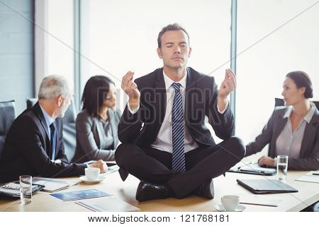 Businessman sitting on table and meditating in conference room