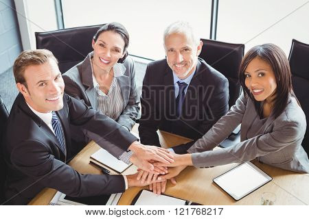 Businesspeople stacking hands in conference room in office
