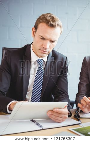 Businessman using digital tablet in conference room