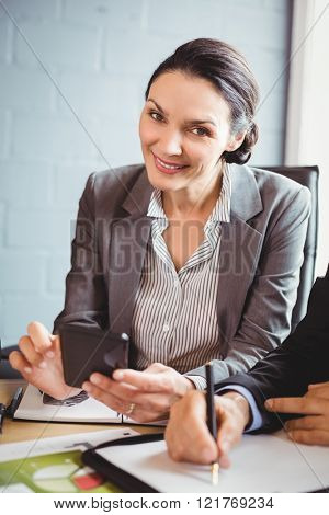 Businesswoman using mobile phone in conference room