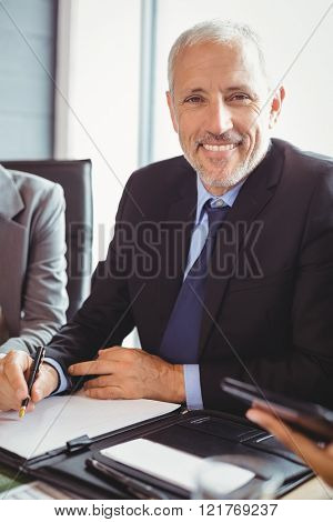 Businessman sitting and writing a report in conference room