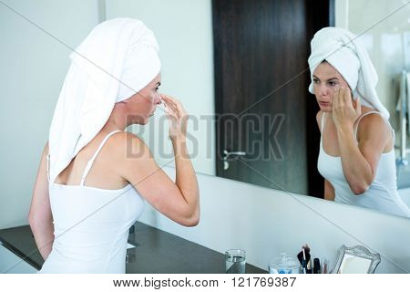 woman with a towel on her head is applying face cream