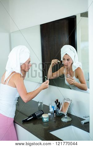 woman wearing a towel on her hair is applying face powder in the mirror