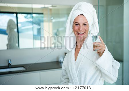 woman wearing a dressing gown and a towel on her head is drinking a glass of water