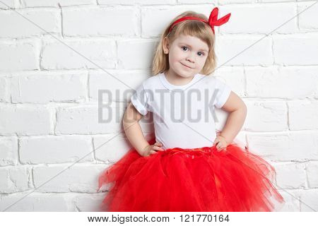 little girl in a red skirt near a white brick wall.