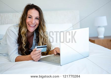 woman lying on her bed on her laptop , smiling at the camera and holding her credit card